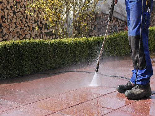 man-pressure-washing-patio